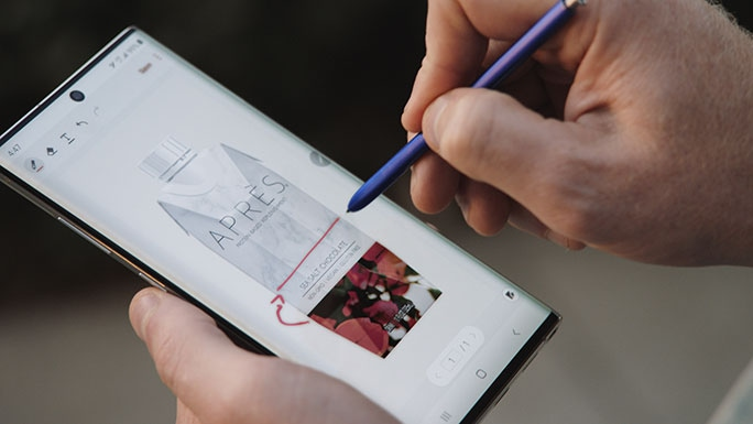 A close-up shot of a Galaxy Note10 and S Pen in Sonny McCracken's hands. On the phone's screen you can see that he is using the S Pen to draw lines on an image of the Après protein drink's packaging.