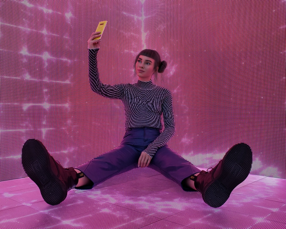 Lil Miquela taking a selfie on a Galaxy S10 while sitting on the ground in a neon-lit room