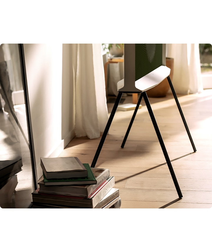 The bottom half of a Cloud White model of The Serif is shown from the side on a black stand in a neat living room, with books in the foreground.