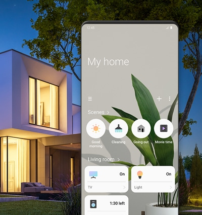 Two-story house that light is on. The SmartThings app screen shows setting conditions for scenes like 'Good morning', 'Cleaning', and 'Going out'. Also shows appliance control option such as TV, Light, and Washer.