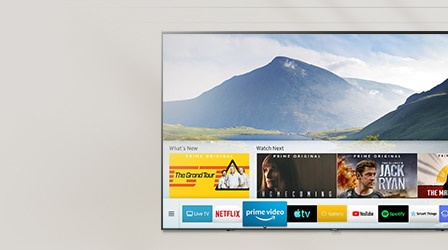 Smart Hub UI is displayed over a nature background image on TV screen; The UI contains various content, such as, 'What's New', 'Watch Next', and several applications like Netflix, Prime Video, Apple TV, Google Play Movies & TV, YouTube, Spotify, SmartThings, Internet, DEEZER.