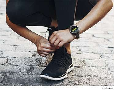 Image of person tying running shoe wearing Gear Sport with Hybrid Sport strap in yellow