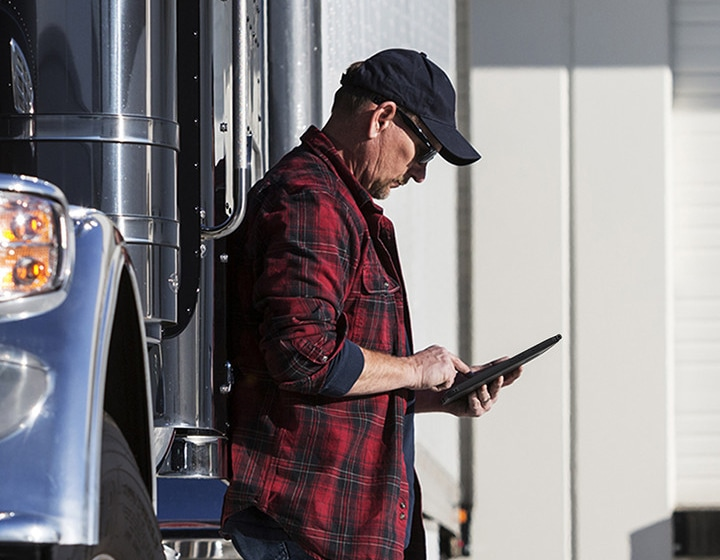 A truck driver leaning on his truck while looking into a Samsung tablet