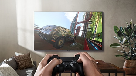 Image of a person playing a racing video game on Samsung Smart TV in a living room.