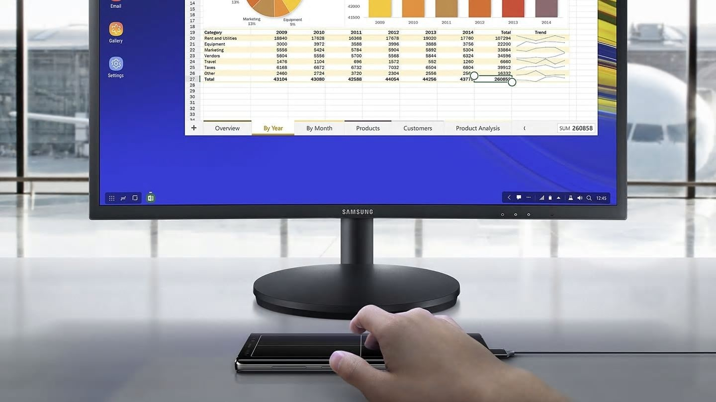 """Simulated image of a person using Galaxy Note9 connected to Samsung DeX via a single cable, looking at a spreadsheet on the connected monitor and using Galaxy Note9 as a touchpad"