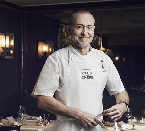 World renowned Michelin starred chef Michel Roux Jr stands in his highly acclaimed restaurant Gavroche, smiling as he puts on his Club des Chefs apron.