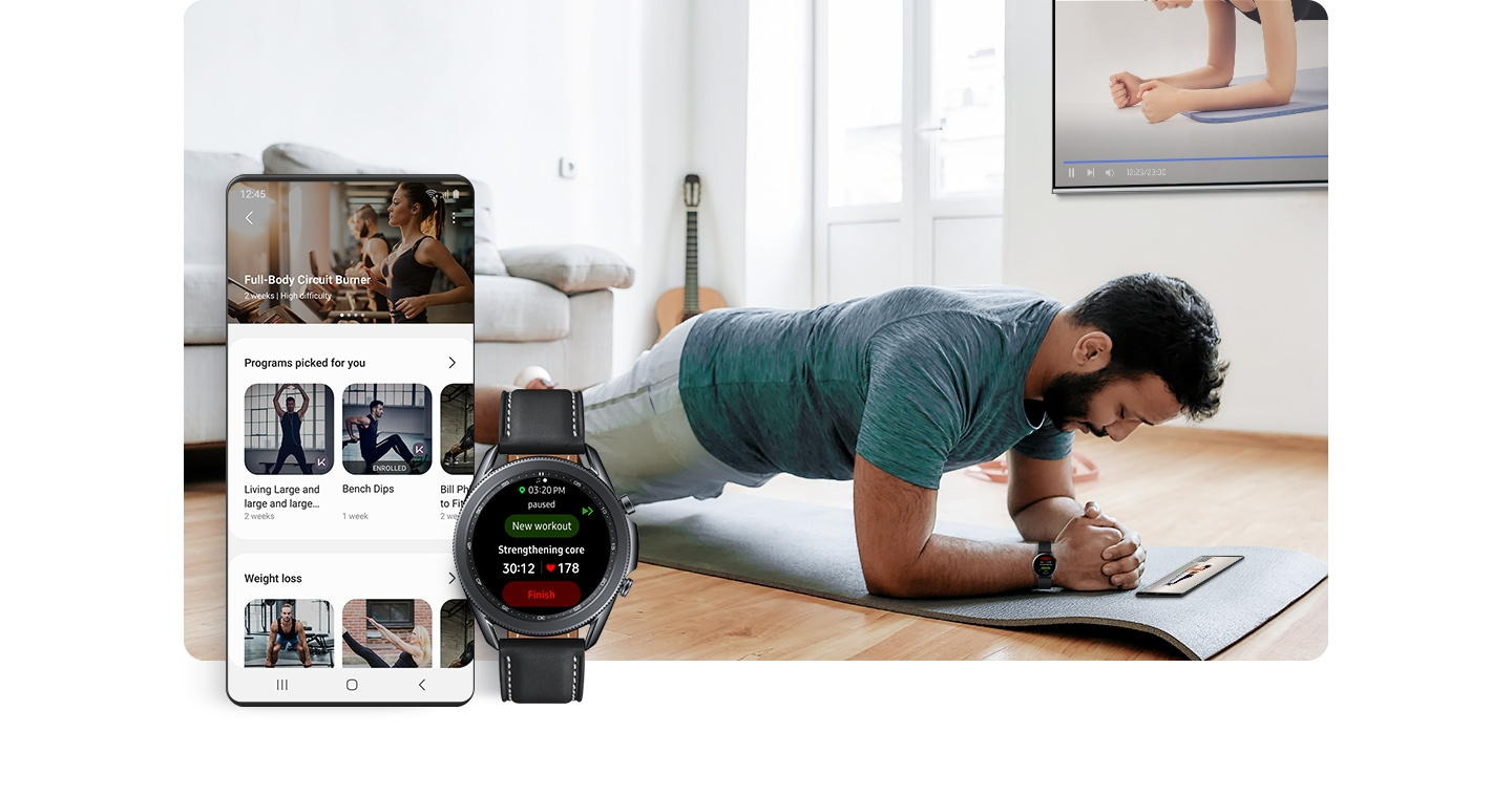 A man wearing a Galaxy Watch is holding a plank position on a mat inside. His workout program is shown on a smartphone on the floor and on the tv on the wall. In the foreground a GUI screen shows various workout programs. A Galaxy Watch screen shows the name of workout and heart rate.