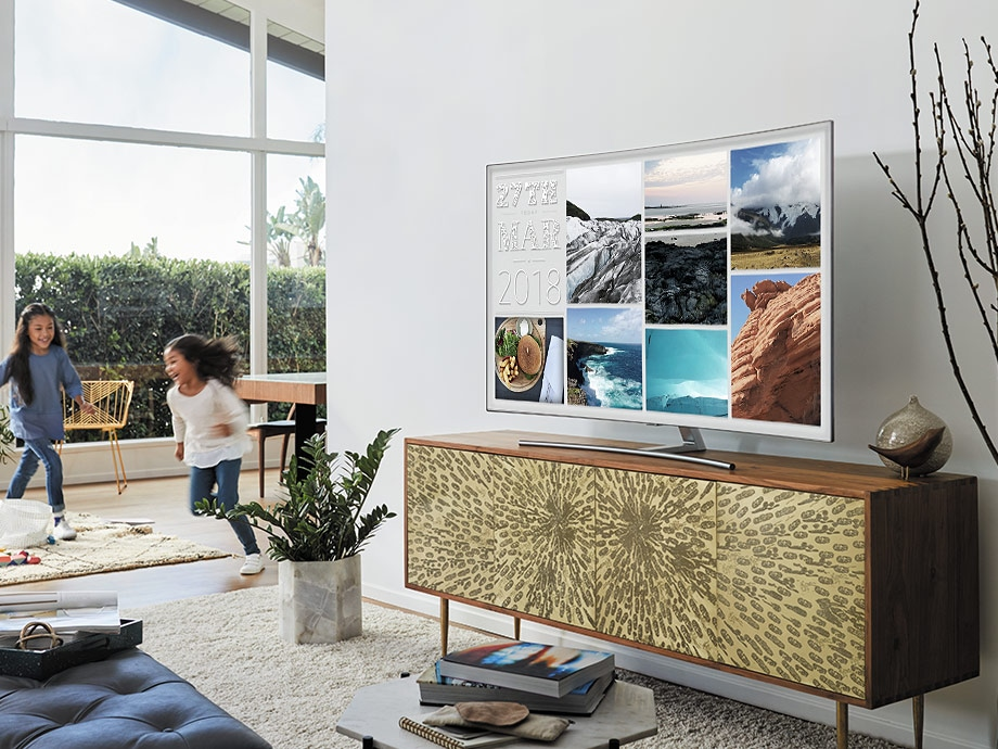 QLED TV is put on a table with its photo mode on and children are playing in the living room. Ambient Mode of QLED TV doesn't just mimic the wall. Make the most out of it with three settings. Deco, Info and Photo mode.