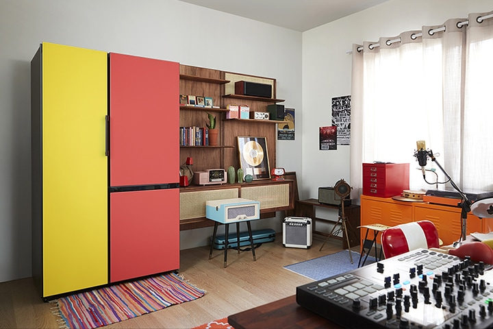 A BESPOKE refrigerator with bright yellow and red doors stands in a colorfully decorated living room filled with retro-style furniture