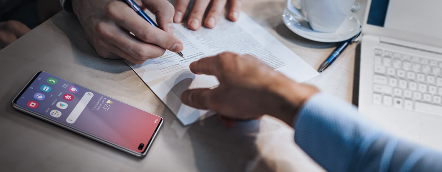 Image of a finance worker pointing out something on a document to their client who is about to sign the document. Galaxy S10 plus is off to the left side on the table.