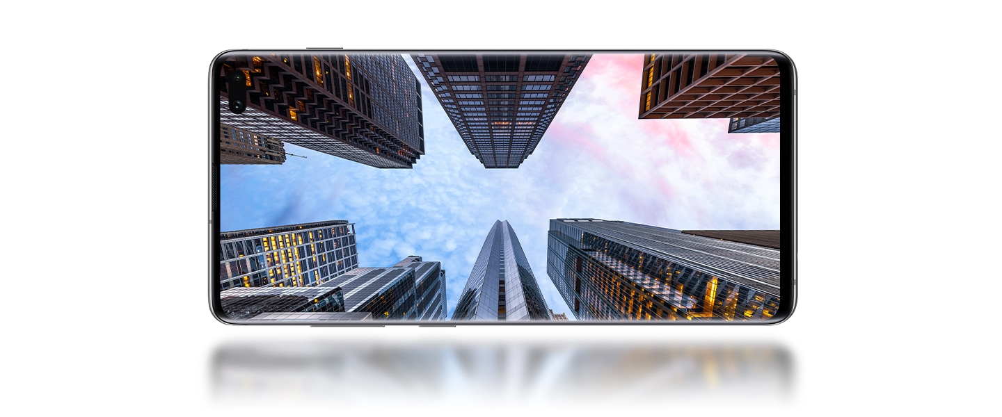 Galaxy S10 plus in landscape mode seen from the front with a photo onscreen of skyscrapers against a dusky sky.
