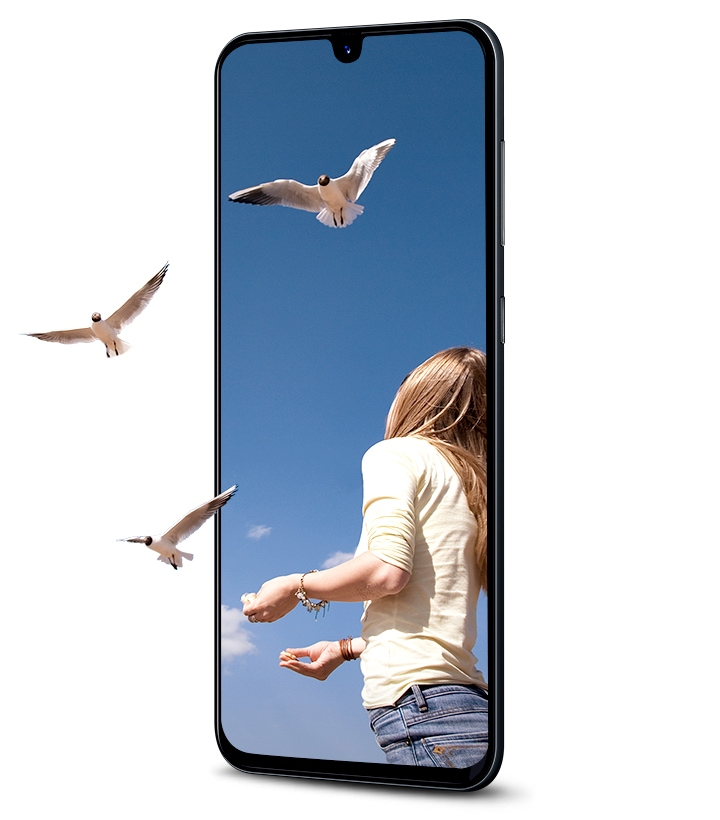 Galaxy A in portrait mode showing a woman releasing birds that fly off the screen to show the immersion of the Infinity Display.