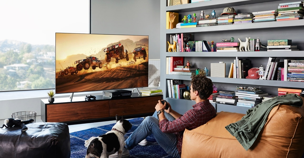 A lifestyle image of the 2018 new QLED TV Q6F. QLED TV is put on a table in the living room and a young man is playing game with QLED TV.