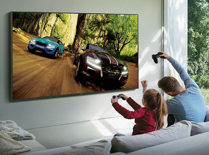 A man and his daughter are playing a Steam game on Samsung Smart TV. The game is being streamed through Samsung Steam Link.