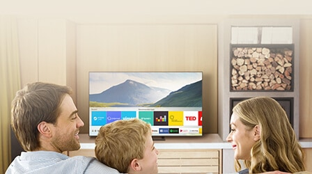 3 people in the living room are watching Smart TV. Smart Hub UI is displayed over a nature background image on TV screen; The UI contains various content, such as, Steam Live, Internet, Vimeo on 'Recent', Tunein Radio, Deezer, Berliner Philharmoniker, TED on 'Recommended Apps' and several applications like YouTube, Facebook Video, Google Play Movies & TV, SmartThings.