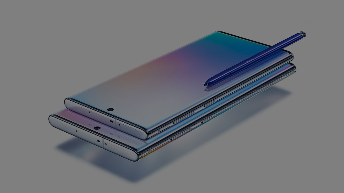 Galaxy Note10 laying on top of Galaxy Note10 plus, both laying on their back at an angle with a blue S Pen laying on top of Galaxy Note10. Each phone has a gradient graphic onscreen.