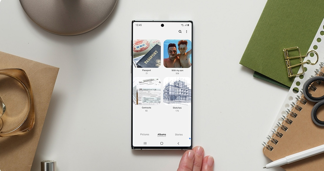 Galaxy Note10 plus laying face up on a desktop with the Secure Folder interface onscreen, showing the Gallery app with albums named Passport, With my son, Contracts, and Sketches. It demonstrates how someone can keep their sensitive work data safe alongside their personal items