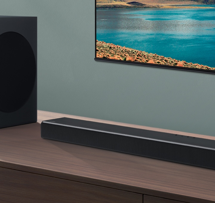 Soundbar and subwoofer are seen on wood cabinets at an angle, with a TV mounted on a wall in the background.