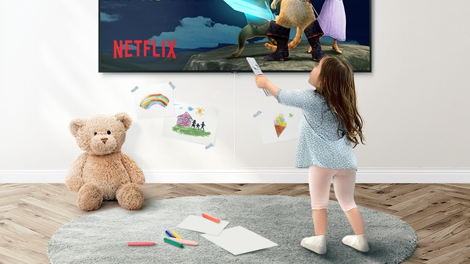 A little kid using smart remote to control QLED TV