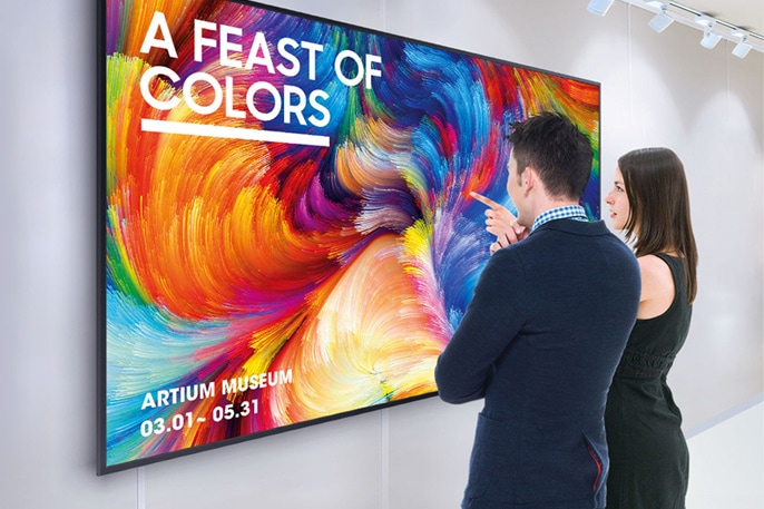 Two people looking at 4k uhd smart signage