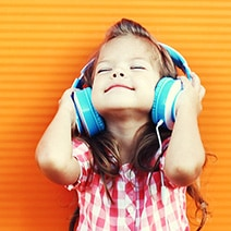 Little girl listening to music with big blue headphones on