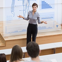 Woman in front of digital board in a classroom