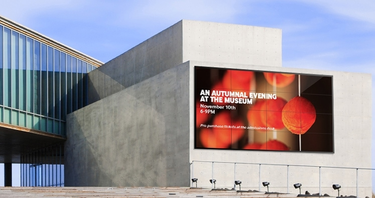 "The exterior of a modern museum with an outdoor wall display announcing ""An Autumnal Evening at the Museum."""