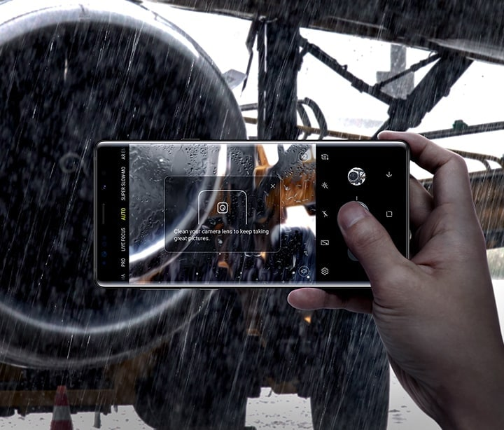 "Image of person holding Galaxy Note9 and taking a photo of a plane engine in the rain, with ""Clean your camera lens to keep taking great pictures"" onscreen, demonstrating Flaw Detection"