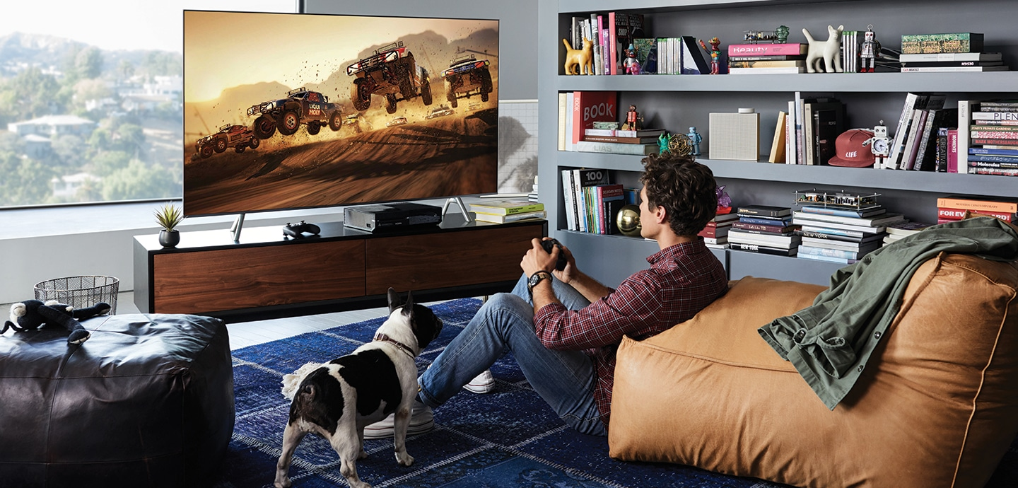 A young man is playing game with QLED TV. Players can complete their gaming experience with its big screen and 4K picture quality with HDR.