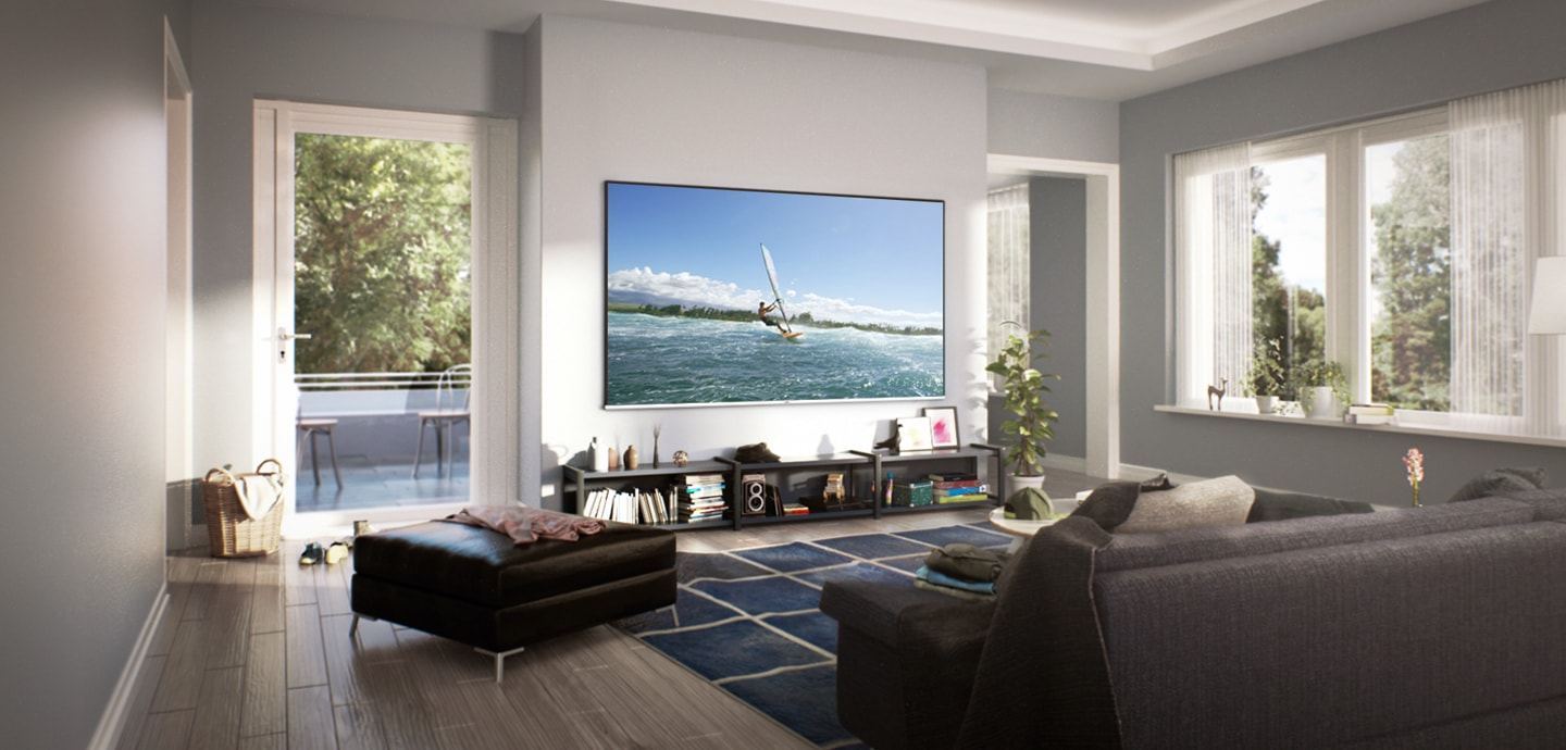 Wide view of cozy living room with daylight from out of the window. Super Big TV is hung on the wall. On the screen, a man is enjoying surfing.