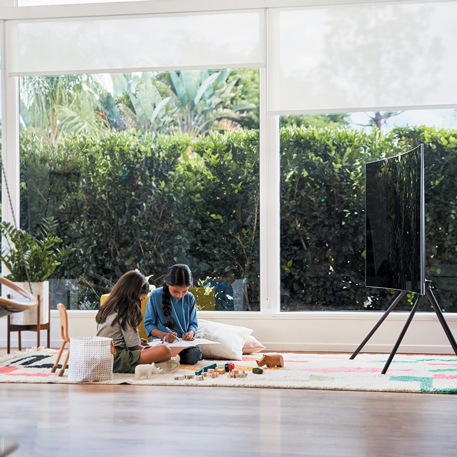 QLED TV is put on a floor with its Studio Stand and children are playing behind it