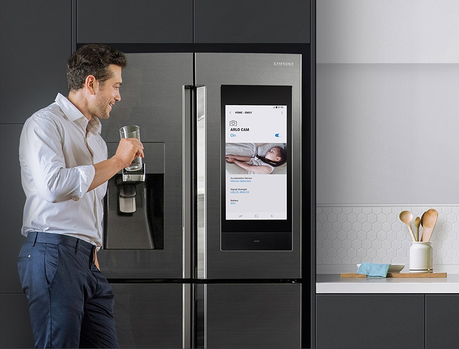 A man drinks a glass of water in the kitchen while checking on his sleeping daughter from the Family Hub screen connected to SmartThings.