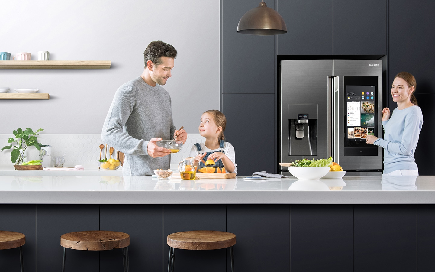 A father and daughter prepare eggs and orange juice on the kitchen counter, as the mother watches over them and smiles while standing next to the Family Hub with the screen in on mode.