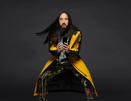 Steve Aoki standing with his knees slightly bent outward while sporting a yellow long coat as he holds up an unfolded Samsung Galaxy Fold smartphone