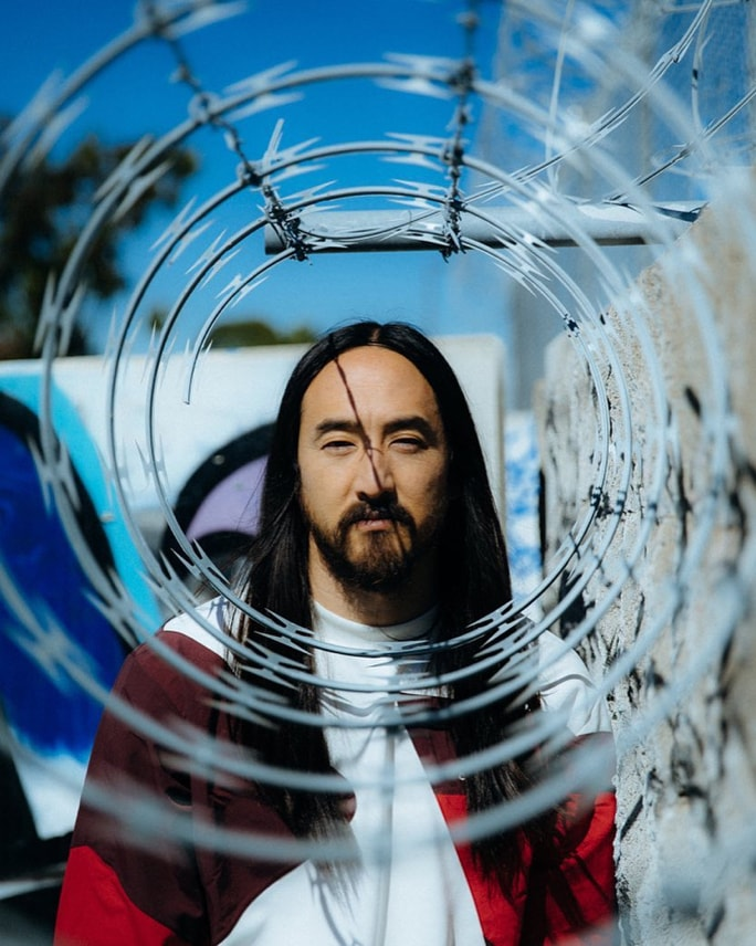A headshot of Steve Aoki gazing seriously through the opening of a barbed wire fence in an urban yard setting