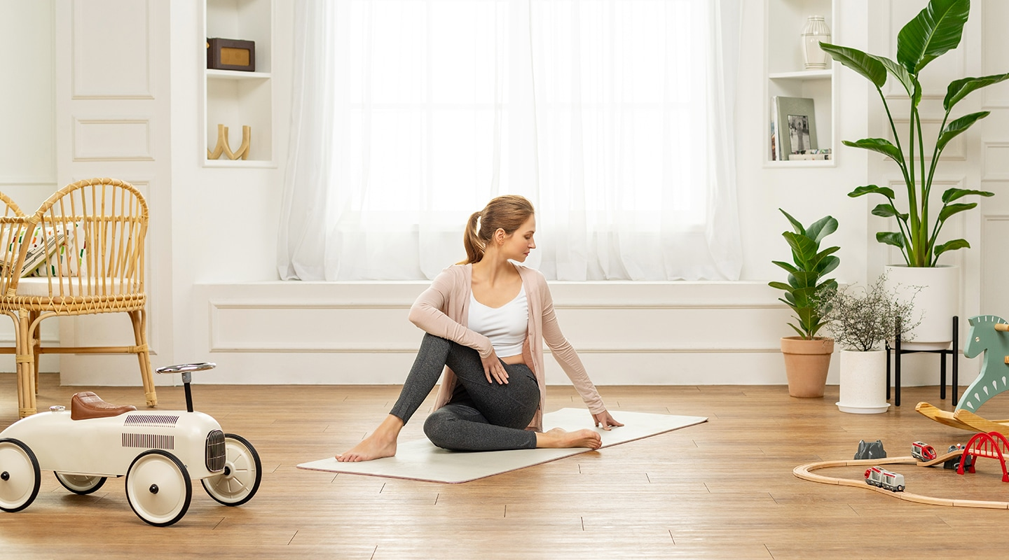 A woman is stretching her full body at home.