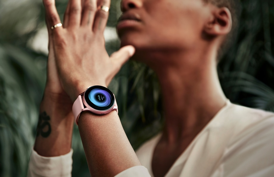 Person meditates while wearing a pink Galaxy Watch Active2 on left wrist
