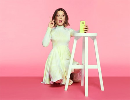 Millie Bobby Brown kneels while holding up a peace sign with her fingers as she takes a selfie with a neon yellow Samsung Galaxy A80 that's propped on a white stool.