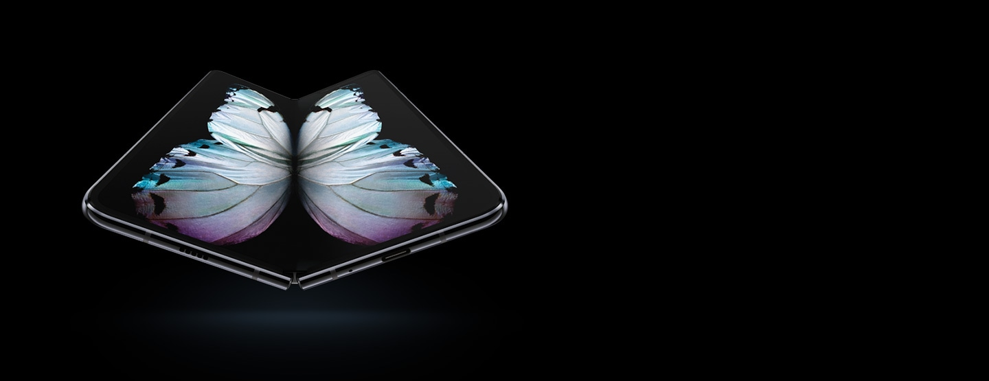 Galaxy Fold in Cosmos Black seen at a slight angle from the bottom, unfolded, with a multicolor butterfly graphic on-screen.