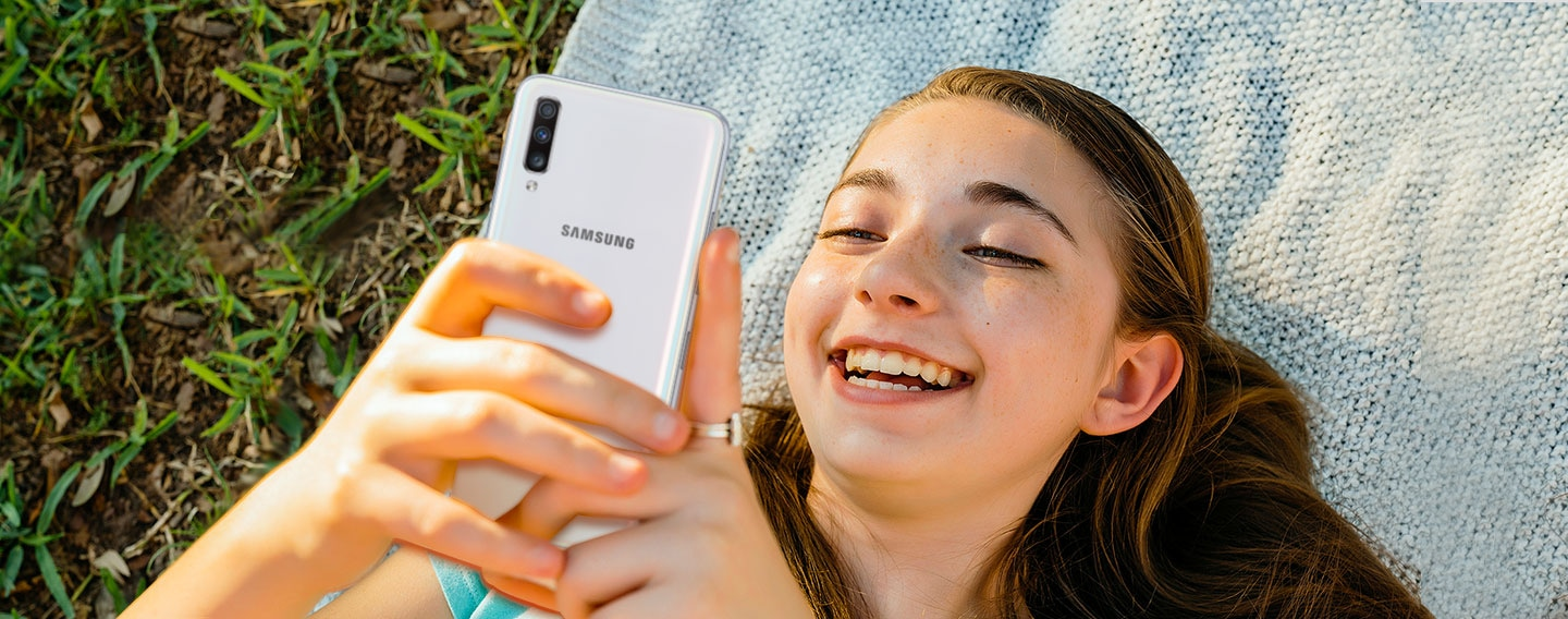 Image of a woman laying on a blanket outside using Galaxy A.