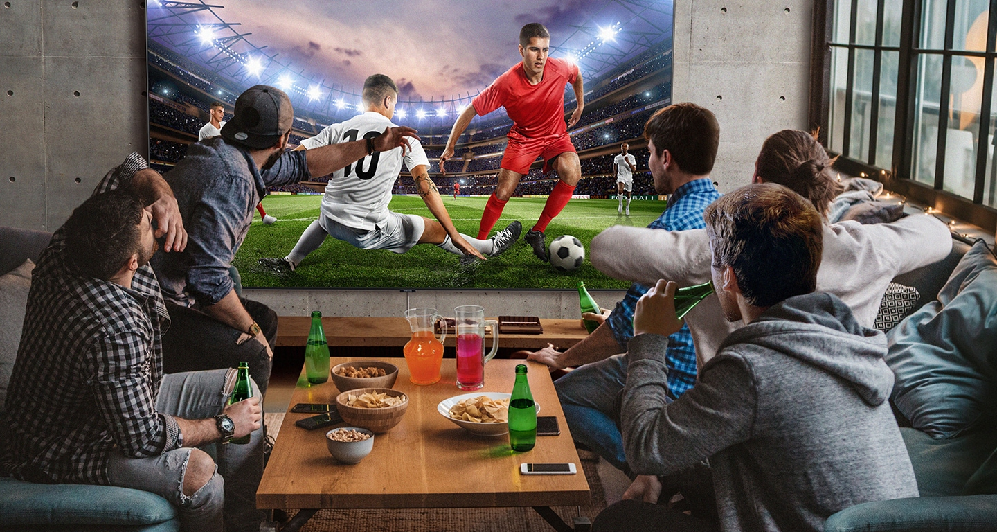 5 men sitting around a mini table with snacks and beverages are watching football game on the large screen TV. With Samsung Super Big TV,  size of living space is no longer a factor.