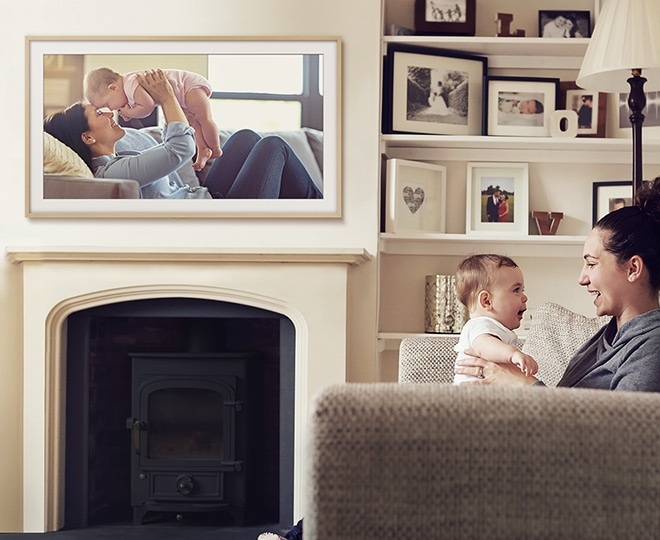 The Frame showing a photograph of a dad and daughter on the beach at sunset in Modern layout with Polar White matte color hanging on the wall above a fireplace in the living room where a mom and her baby are smiling at each other on the sofa.