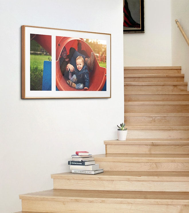 The Frame showing a family photograph in a Mix layout with Polar White matte color is on the wall next to a staircase in a home.