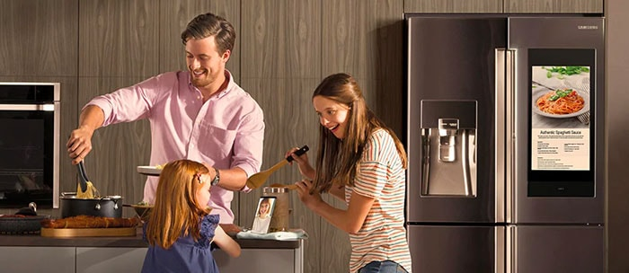 A family of three is seen happily cooking dinner in the kitchen together.
