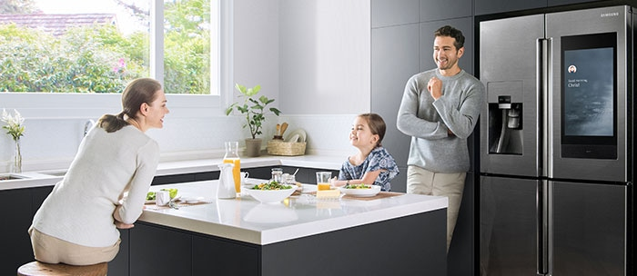 A family of three enjoys breakfast in the kitchen, while standing in front of the Family Hub refrigerator.