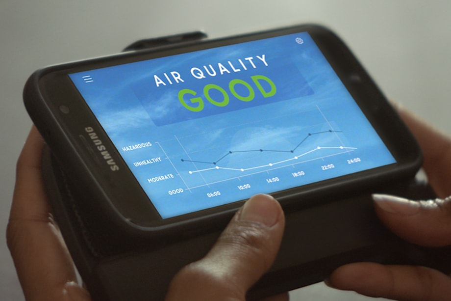 Two hands holding a used Galaxy mobile device, displaying an air quality measuring device.