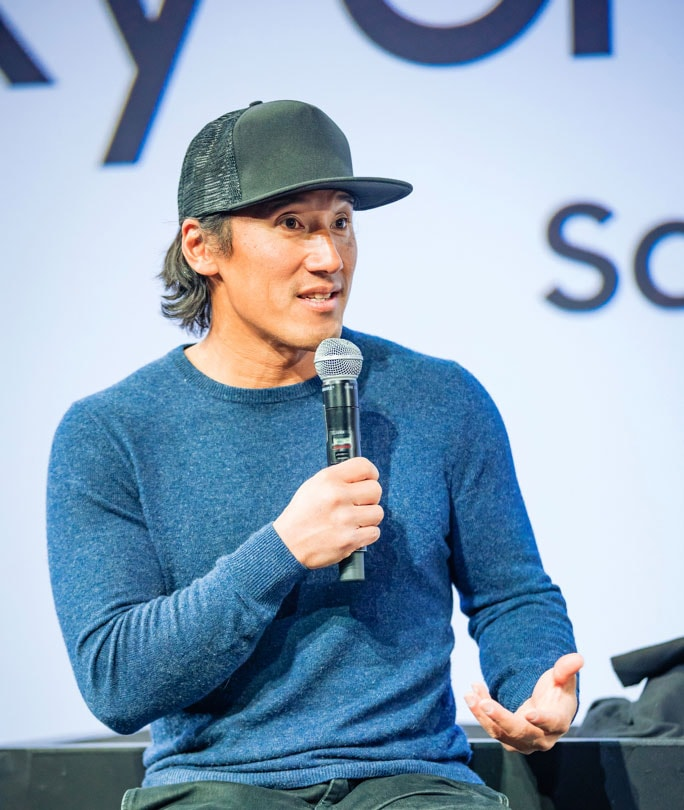 Jimmy Chin wearing a baseball cap and a blue sweater and speaking on stage at the Creator Lounge Creators Talk