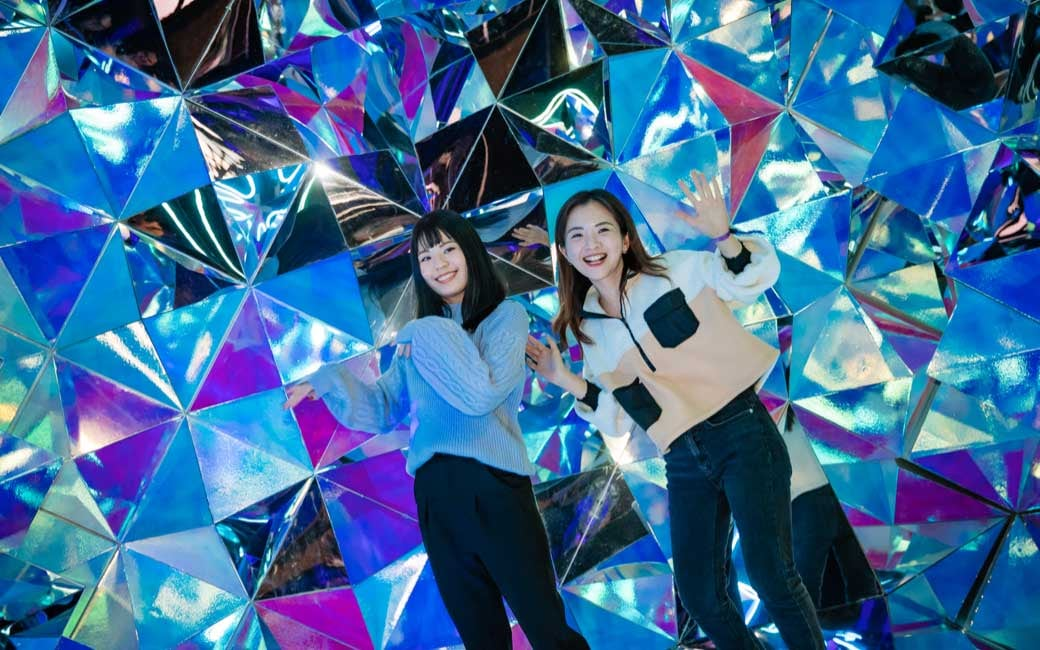 Two ladies make shapes with their arms and strike fun poses while facing the camera, they are in a kaleidoscopic room