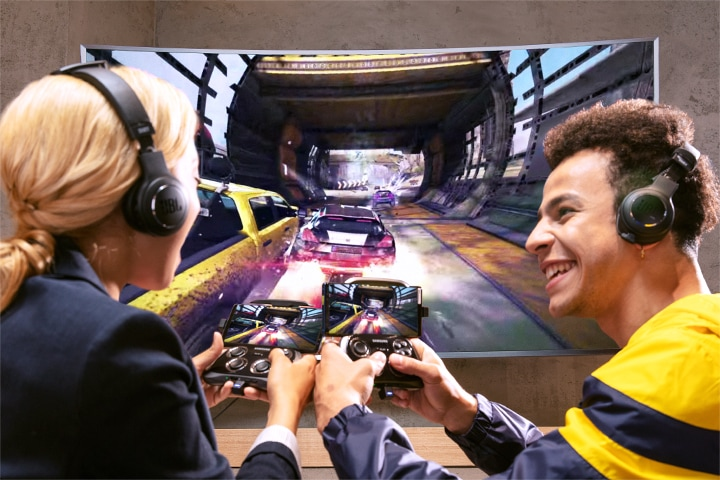 A man and a woman with headphones on and smartphones connected to a tv, using them as controllers for a game on the large screen