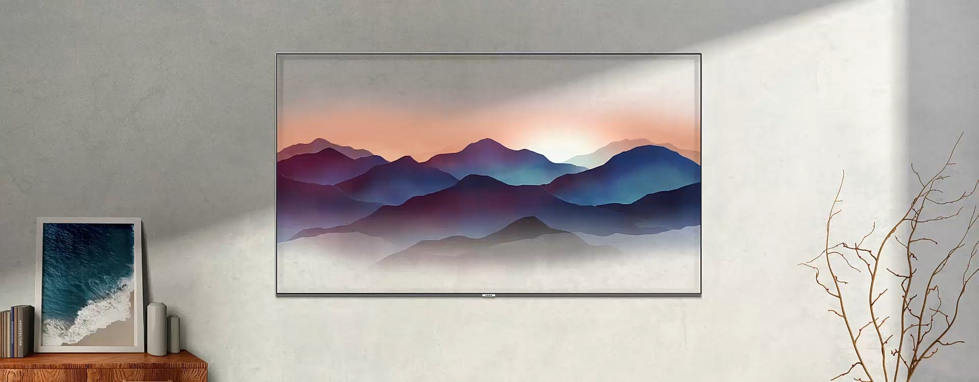 A video shows the various options for Ambient Mode. In Deco Mode, an image of mountains in the QLED TV on the wall is moving naturally. The room goes dark as the time changes from day to night. In Info Mode, the QLED TV shows the current location and temperature. The screen goes dark as the time changes from day to night. In Photo Mode, photo list appears on the Samsung QLED TV. The screen focuses in on the selected picture. In Music Mode, A notification for playing music appears on the QLED TV on the wall